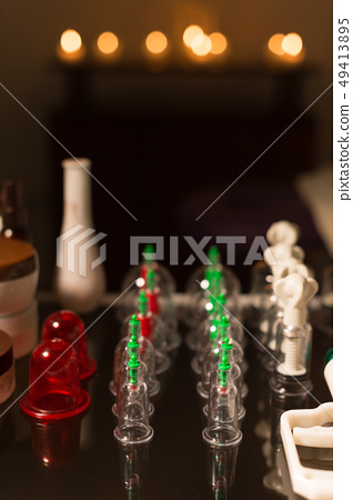 Medical set of glass jars and piston vacuum massage in a dark room amid burning candles 49413895