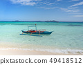 A small blue boat on a tropical beach 49418512