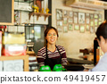 Young woman barista serving customer with smile face at counter bar in cafe. 49419457