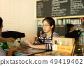 Young barista taking money from customer pay for beverage at coffee shop. 49419462