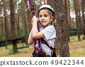 Girl climber hanging on insurance in the forest 49422344