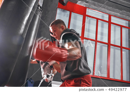 Ready to break his record. Young muscular athlete in sports clothing training hard on heavy punch 49422977