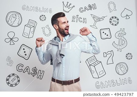 Time to take a break. Young bearded man feeling tired and yawning with raised hands while standing 49423797
