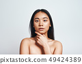 Perfect skin. Portrait of beautiful asian woman touching her skin and looking at camera while 49424389
