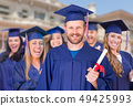 Group of Graduates In Cap and Gown Celebrating 49425993