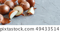 Yellow onions on a grey board 49433514