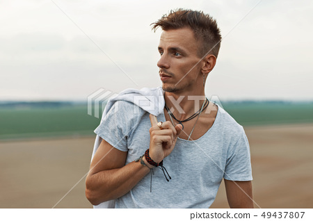 Handsome man with hair holds jacket 49437807