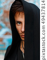 Portrait of a handsome man in a black hood. 49437814