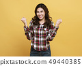 Portrait surprised happy asian woman on yellow 49440385