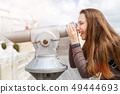 Young tourist girl watching city through telescope 49444693
