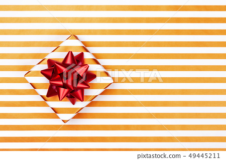 Top view of gift box on striped paper with red bow. 49445211