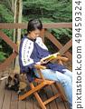 우드 데크에서 독서를하는 여자와 개 49459324