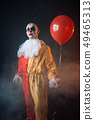 Bloody clown in carnival costume holds air balloon 49465313