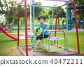 Young Asian boy play a iron train swinging at the 49472211