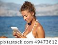 Beautiful woman reading ebook on the beach 49473612