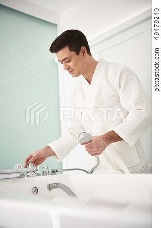Waist up of man regulate tap power in spa bath 49479240