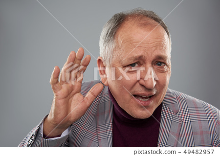 Man putting hand near the ear while listening attentively 49482957