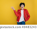 Joyful stylish old lady putting her hand in pocket on yellow background 49483243