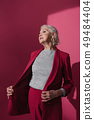 Confident elderly lady posing in studio and looking aside 49484404