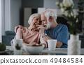Positive elder couple drinking tea with cookies 49484584