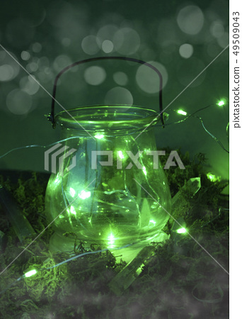 Magic cauldron on green background with moss and f 49509043