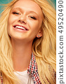 Portrait of an attractive blond woman in a plaid shirt is smiling and looking at the camera. 49520490