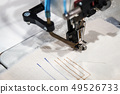 Sewing machine makes a stitch on the fabric 49526733