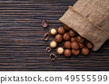 Macadamia nuts in bag  on wooden table 49555599