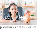 Asian little girl in putting coin in to piggy bank 49558171