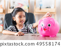 Asian little girl in putting coin in to piggy bank 49558174