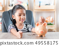 Asian little girl in putting coin in to piggy bank 49558175