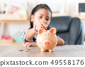 Asian little girl in putting coin in to piggy bank 49558176
