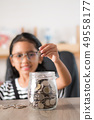 Asian little girl in putting coin in to glass jar 49558177