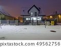 New house with stone fence at snowy night 49562756