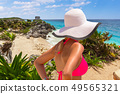 Woman in hat at beautiful Tulum beach by Caribbean 49565321