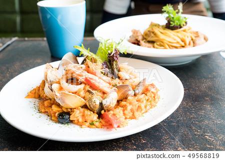 美味的平底鍋炒海鮮飯。頂面茄子,鮭魚,煎餅,海鮮。 49568819