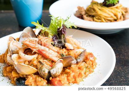 美味的平底鍋炒海鮮飯。頂面茄子,鮭魚,煎餅,海鮮。 49568825