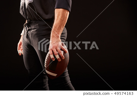 Mid section of American football player with ball against black, copy space, side view 49574163
