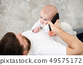 Father put phone to baby girl ear 49575172