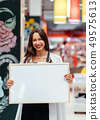 Smiling brunette woman holding white blank board 49575613