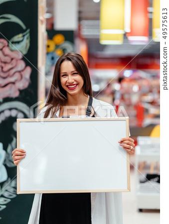 Smiling brunette woman holding white blank board 49575613