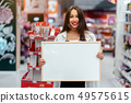 Smiling brunette woman holding white blank board 49575615