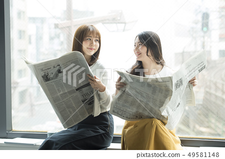 Two women reading a newspaper on the window side 49581148
