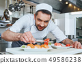 Made Fresh Always. Sushi master prepares sushi for serving in modern commercial kitchen 49586238