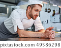 We know our food. Male chef leaning on the table and looking aside while going to cook 49586298