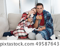 Sick Couple Sitting on Sofa in Checkered Blankets. 49587643