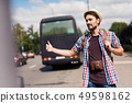 Young Tourist with Backpack Hitchhiking on Road 49598162
