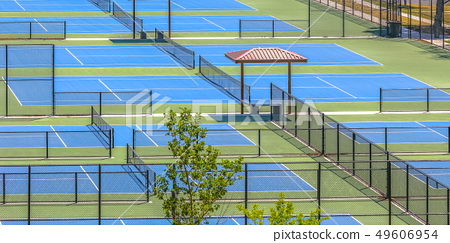 View of side by side tennis courts on a sunny day 49606954