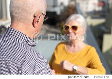 Elderly, deaf man uses a hearing aid 49608178