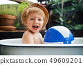 Small boy with a ball in bath outdoors in garden in summer, playing in water. 49609201